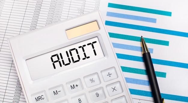На фоне отчетов и синих графиков ручка и белый калькулятор с тестом на экране аудит. бизнес-концепция
