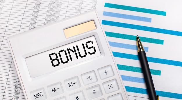 На фоне отчетов и синих графиков ручка и белый калькулятор с тестом на бонусном экране. бизнес-концепция