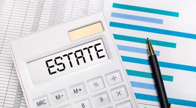 На фоне отчетов и синих графиков ручка и белый калькулятор с тестом на экране недвижимости. бизнес-концепция