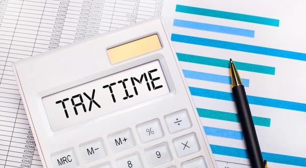 На фоне отчетов и синих графиков ручка и белый калькулятор с тестом на экране налоговое время. бизнес-концепция