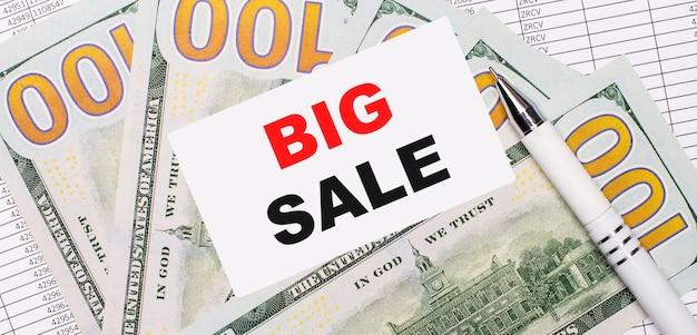 На фоне отчетов и долларов - белая ручка и карточка с текстом большая распродажа. бизнес-концепция