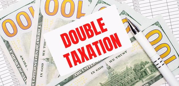 На фоне отчетов и долларов - белая ручка и карточка с текстом двойное налогообложение. бизнес-концепция