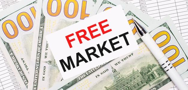 보고서와 달러를 배경으로 - 흰색 펜과 free market이라는 텍스트가 있는 카드. 비즈니스 개념