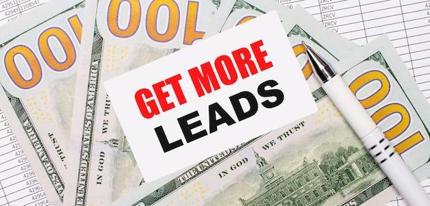 На фоне отчетов и долларов - белая ручка и карточка с текстом получить больше ведущих. бизнес-концепция