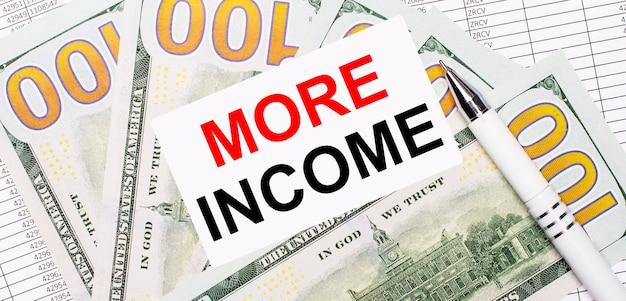 レポートとドルを背景に-白いペンと「moreincome」というテキストのカード。ビジネスコンセプト