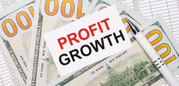 На фоне отчетов и долларов - белая ручка и карточка с текстом рост прибыли. бизнес-концепция