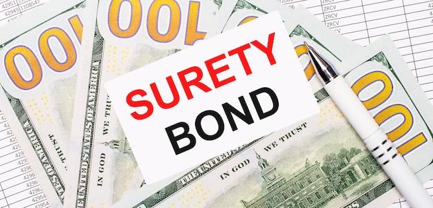 На фоне отчетов и долларов - белая ручка и карточка с текстом surety bond. бизнес-концепция