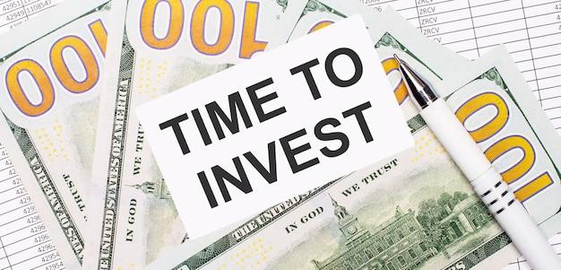 На фоне отчетов и долларов - белая ручка и карточка с текстом «время инвестировать». бизнес-концепция