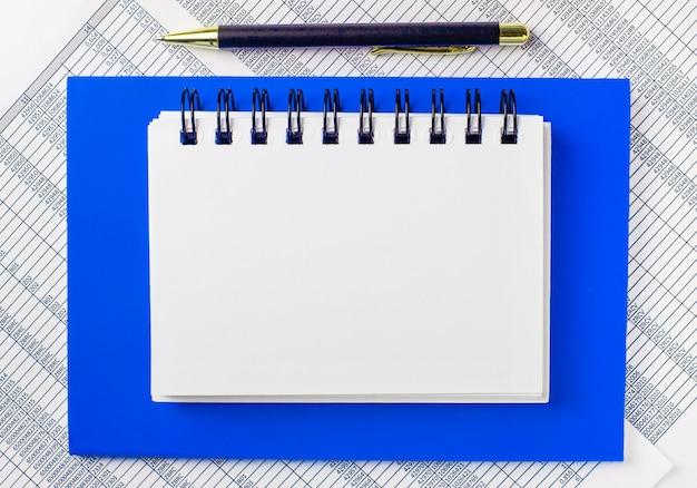 デスクトップ上のレポートを背景に、青いメモ帳。ペンと、テキストを挿入するスペースのあるきれいな白いノートがあります。テンプレート。ビジネスコンセプト Premium写真