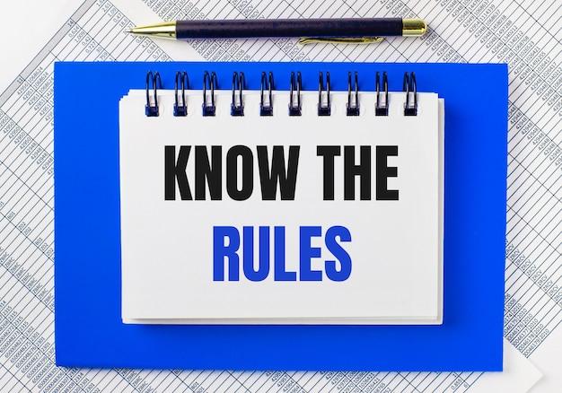 На фоне отчетов на рабочем столе синий блокнот. у него есть ручка и белый блокнот с текстом «знайте правила». бизнес-концепция