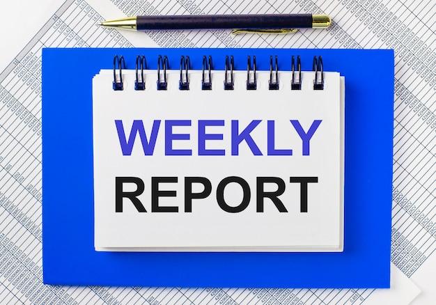 На фоне отчетов на рабочем столе синий блокнот. в нем есть ручка и белый блокнот с текстом еженедельный отчет. бизнес-концепция