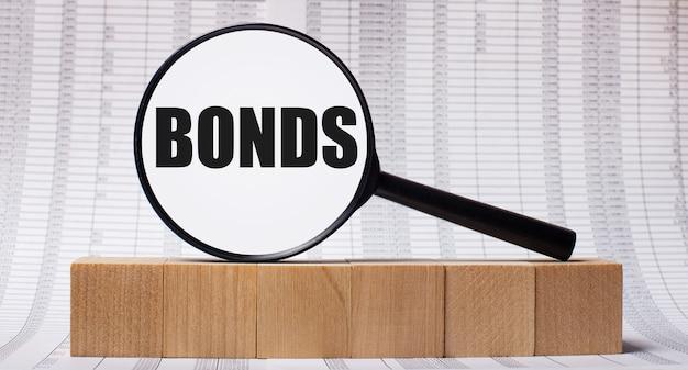 На фоне отчетов о деревянных кубиках - увеличительное стекло с текстом bonds. бизнес-концепция