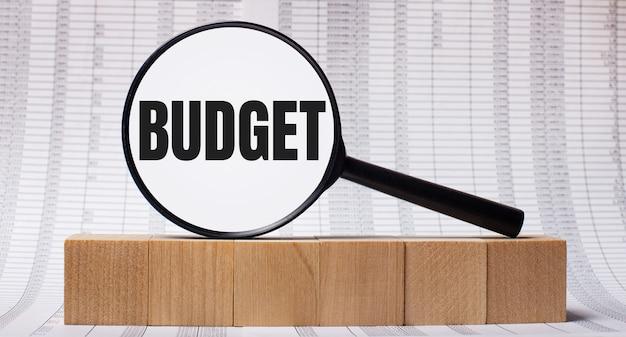 На фоне отчетов о деревянных кубиках - увеличительное стекло с текстом бюджет. бизнес-концепция