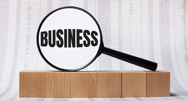 木製の立方体に関するレポートを背景に、businessというテキストが付いた虫眼鏡。ビジネスコンセプト