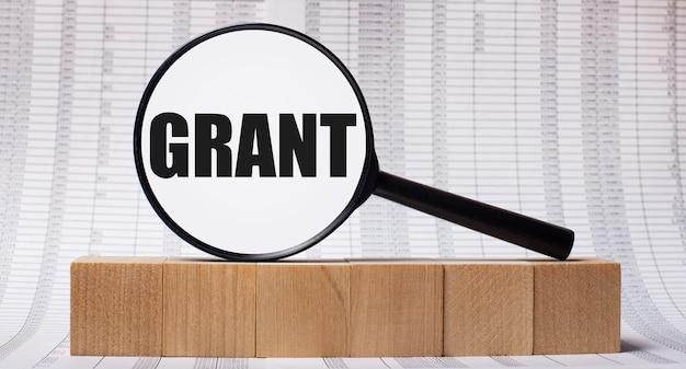 На фоне отчетов о деревянных кубиках - увеличительное стекло с текстом grant. бизнес-концепция