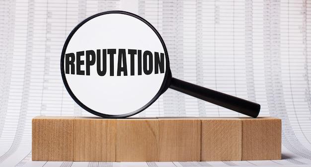 На фоне отчетов о деревянных кубиках - увеличительное стекло с текстом репутация. бизнес-концепция