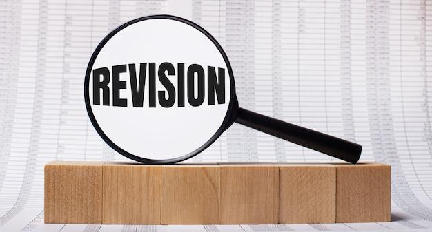 木製の立方体に関するレポートを背景に、revisionというテキストが付いた虫眼鏡。ビジネスコンセプト