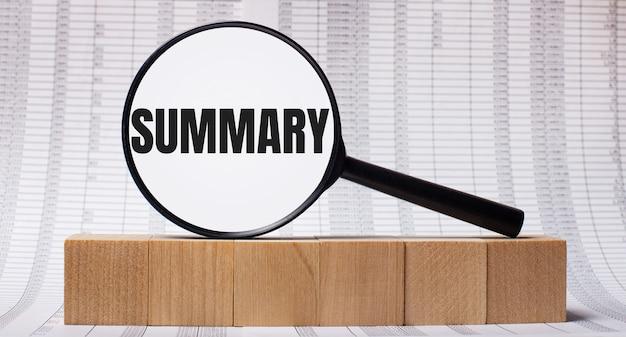 木製の立方体に関するレポートを背景に、summaryというテキストが付いた虫眼鏡。ビジネスコンセプト