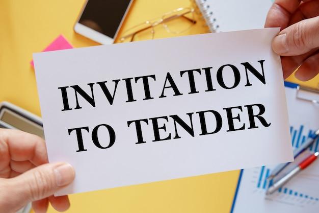 사무실 테이블의 배경-입찰 초대장 텍스트가있는 카드.