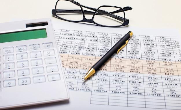 На фоне отчетов ручка, белый калькулятор и очки в черной оправе. бизнес-концепция. на рабочем месте крупным планом