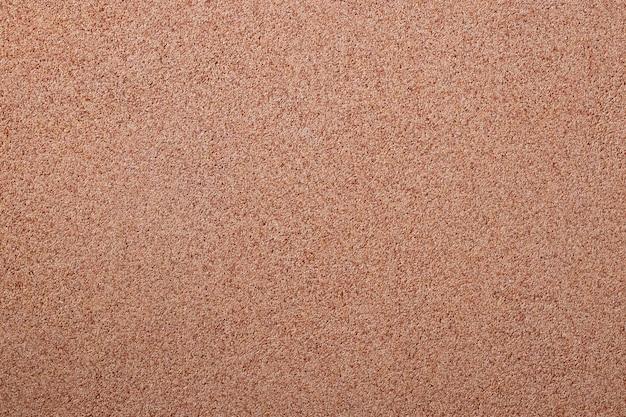 散在する砂の小さな砂利に対して、石のパン粉。壁の表面の質感、明るい色。