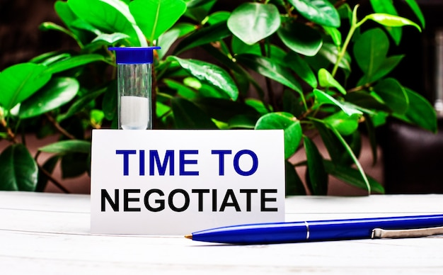 植物の緑の葉の表面に対して、テーブルの上にペン、砂時計、そして「ngotiateする時間」と書かれたカードがあります。