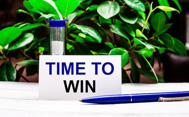На фоне зеленых листьев растения на столе ручка, песочные часы и карточка с надписью time to win.