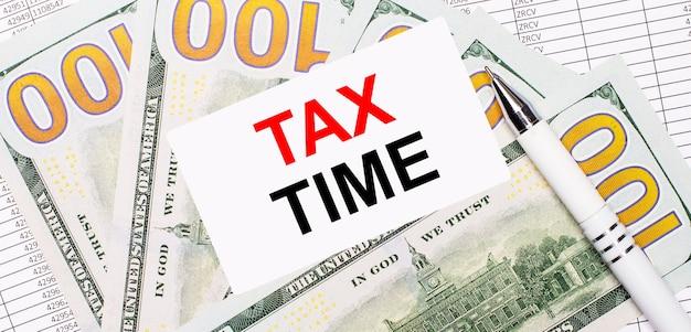 На поверхности отчетов и долларов - белая ручка и карточка с текстом налоговое время.