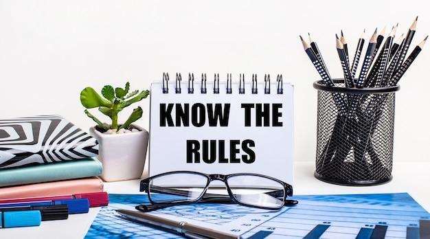파란색 계획의 벽과 흰 벽, 스탠드의 검은 색 연필, 꽃, 일기 및 비문이있는 노트 know the rules