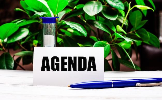 У стены из зеленых листьев растения на столе ручка, песочные часы и открытка с надписью agenda.