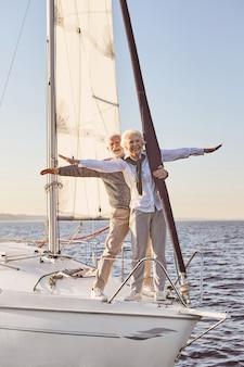 風に逆らって浮かぶ帆船やヨットデッキの横に立っている幸せな年配のカップル