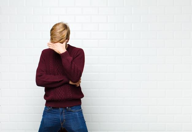 探している若いブロンドの男を強調した、恥ずかしいまたは動揺、頭痛、手agaistヴィンテージタイル壁で顔を覆っている