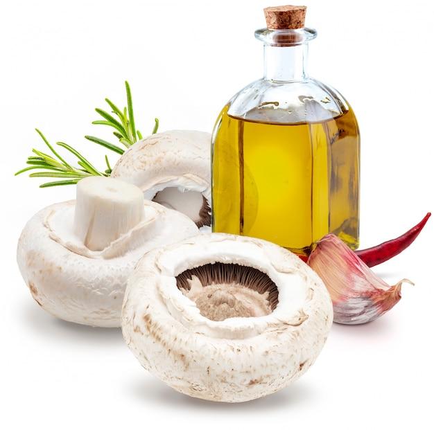 Сырые грибы с перцем чили, оливковым маслом и розмарином фреко (шампиньоны, порезанная ножка, agaricus bisporus). изолированные на белом фоне