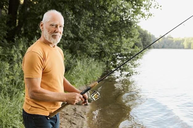 나이, 활동 및 여가 개념. 은퇴 한 수석 수염 난 남성의 측면보기는 물고기가 구부러지기를 기다리는 피셔로드가있는 강둑에서 낚시하는 동안 편안하고 행복합니다.