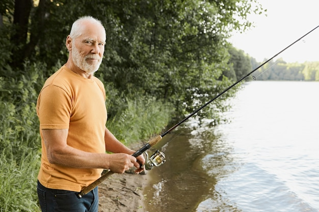Age, activity and leisure concept. side view of retired senior bearded male feeling relaxed and happy while fishing on river bank with fisher rod cast in water, waiting for fish to be hooked