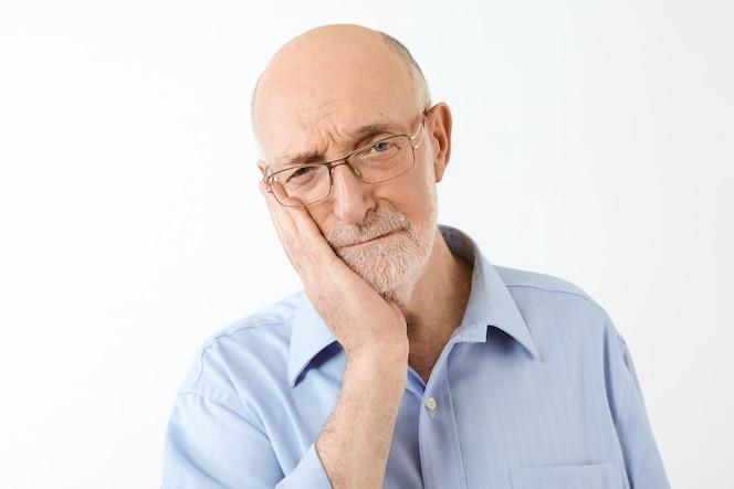 나이와 성숙한 사람들 개념. 대머리 머리와 두꺼운 수염이 뺨을 만지고, 참을 수없는 치통으로 고통 받고, 비참한 고통스러운 표정을 가진 화가 유럽 남성 연금의 고립 된 샷