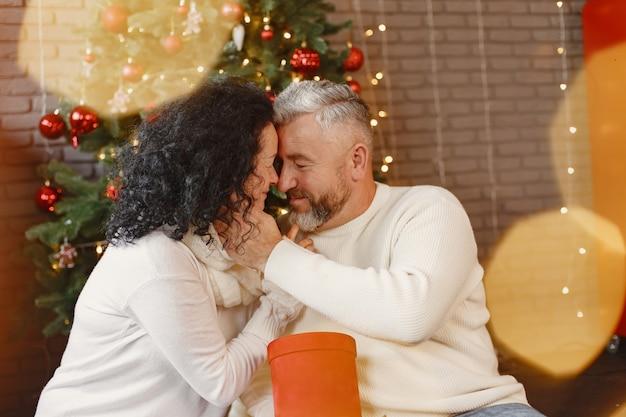 年齢と人の概念。自宅で年配のカップル。白いニットのセーターを着た女性。
