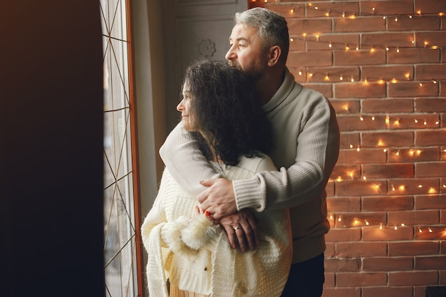 Возраст и концепция людей. старшие пары с подарочной коробкой на фоне огней. женщина в белом трикотажном комбинезоне.