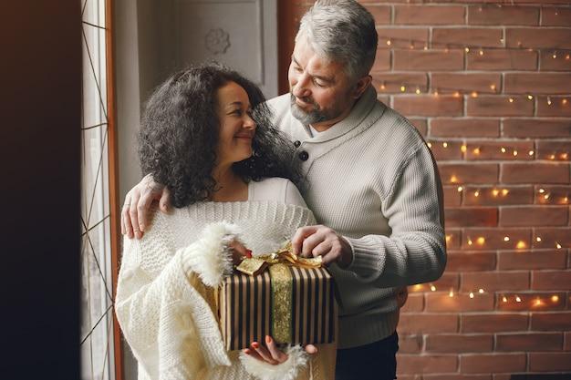年齢と人の概念。ライトの背景にギフトボックスと年配のカップル。白いニットのセーターを着た女性。