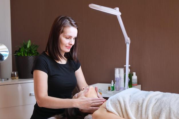 Возраст, красота, лицо, концепция лечения. женщина средних лет в кабинете косметолога, получает антивозрастной массаж
