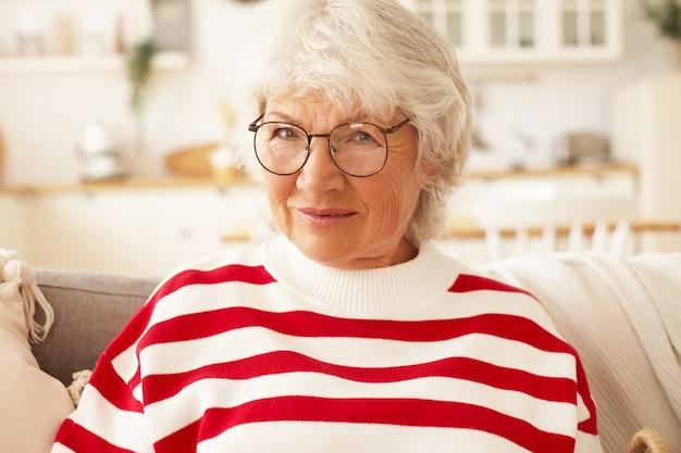나이, 성숙한 사람, 라이프 스타일 및 은퇴 개념. 세련 된 스트라이프 셔츠와 안경을 집에서 편안 하 게 웃 고 행복 한 매력적인 노인 은퇴 한 여자의 총을 닫습니다