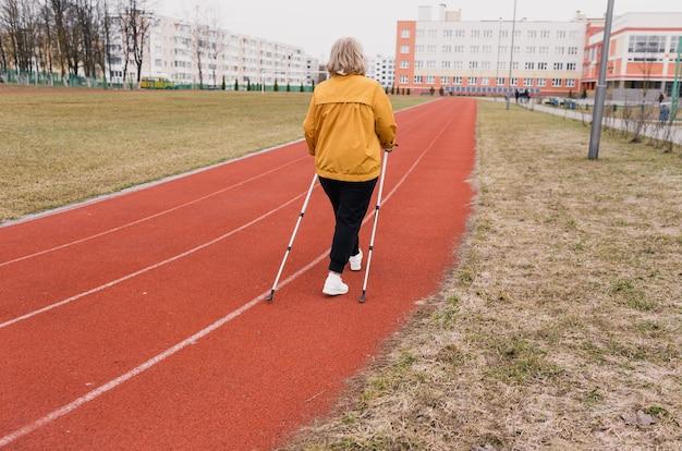 Возрастная зрелость, активный образ жизни и благополучие. счастливый пенсионер с тростью в желтой куртке на стадионе. пожилая пожилая женщина отдыхает после скандинавской ходьбы. утренняя тренировка.