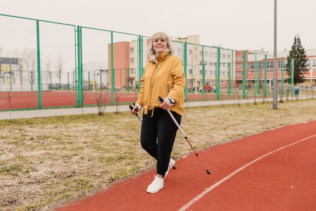 Age maturity, active lifestyle and well-being. a happy pensioner with walking sticks in a yellow jacket at the stadium. an elderly elderly woman rests after a nordic walk. morning workout.