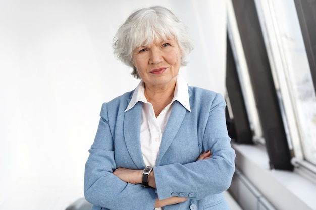 Age, maturiy, job, style and elegance concept. waist up shot of skilled female boss in her sixties posing by window at her office, keeping arms crossed, looking with serious confident smile