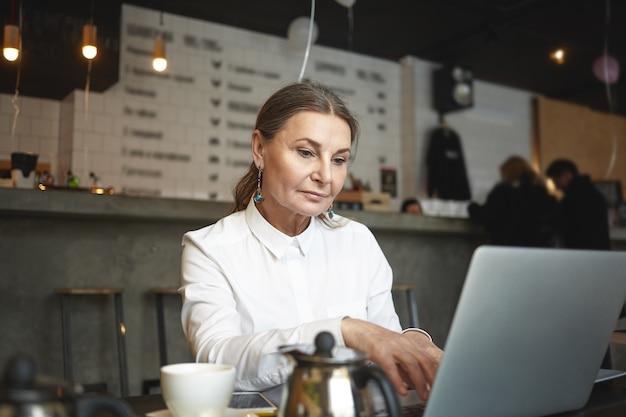 나이, 직업, 프리랜서 및 원격 작업 개념. 커피 하우스에서 노트북에서 고속 인터넷 연결을 사용하여 먼 프로젝트에서 작업하는 아름다운 성숙한 게리 머리 유럽 여성 프리랜서