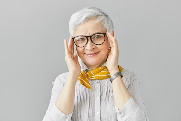 Age, optics, eyewear and vision concept. smiling good looking elegant retired mature female having joyful facial expression, adjusting stylish eyeglasses in black frame, wearing shirt and scarf