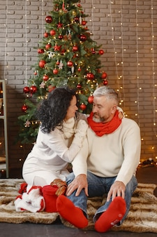 Age and people concept . senior couple at home. woman in a white knited sweater.