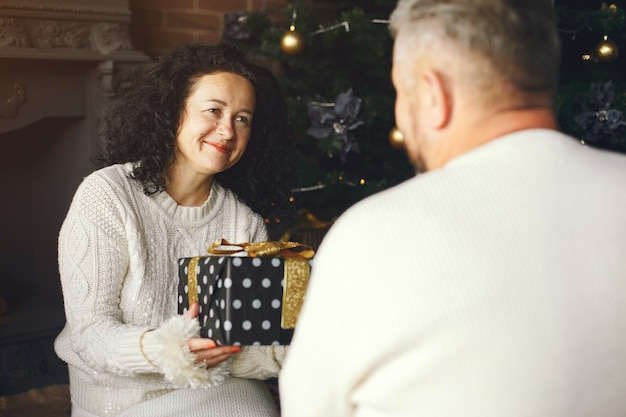 Age and people concept . senior couple with gift box over lights background. woman in a white knited sweatre.