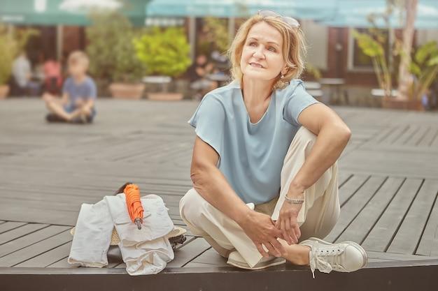 약 62 세의 적극적이고 쾌활한 노인 백인 백인 여성이 공공 공원에서 쉬고 있습니다.