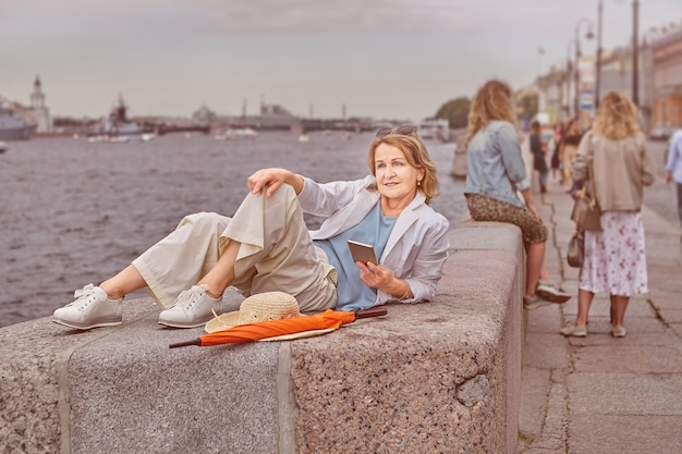 Aged active charming caucasian woman about 62 years old has  rest near river in casual and elegant cloth with cell phone in hands in saint petersburg.